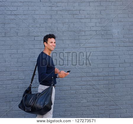 Attractive Man Walking With Mobile Phone And Bag