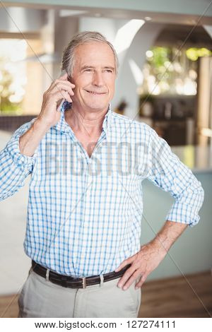 Smiling senior man talking on mobile phone while standing at home