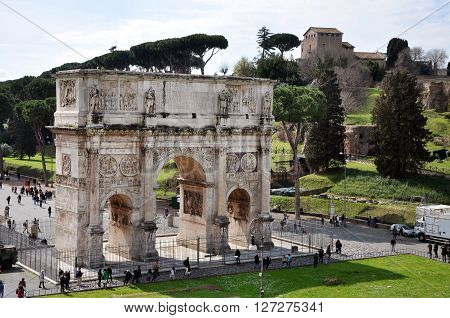 ROME ITALY - MARCH 16 2016: Tourist visiting the triumphal Arch of Constantine near the Colosseum in Rome Italy
