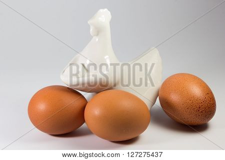 Porcelain Figurine Of Chicken And Eggs On White Background