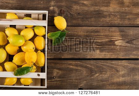 Top view of juicy yellow lemons with leaves in crate on old wooden background with copy space.