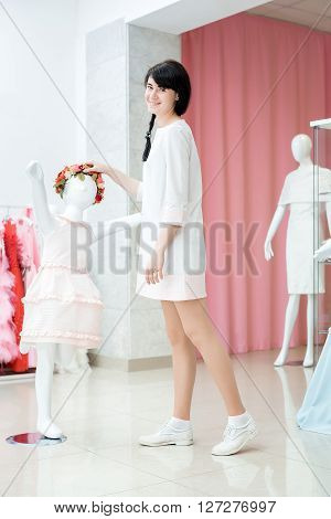 Girl Adjusts Dress On The Mannequin