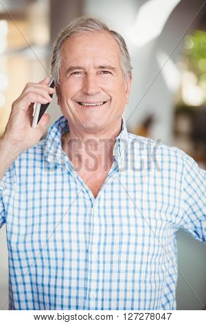Happy senior man talking on mobile phone while standing at home
