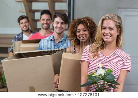Portrait of friends smiling while carrying boxes in new house