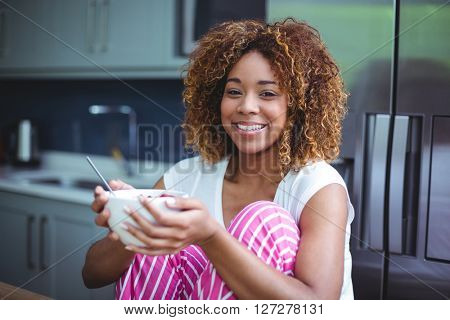 Portrait of happy woman having breakfast in kitchen at home
