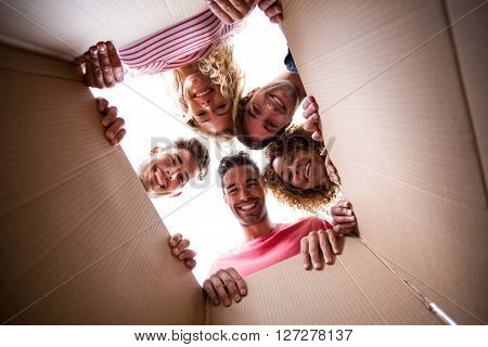 Low angle portrait of cheerful friends seen through cardboard box in new house