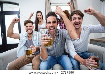 Young friends cheering and drinking alcohol while watching soccer match at home