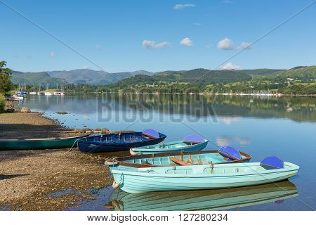 Rowing boats for hire for pleasure and leisure by beautiful lake and mountains on calm still day