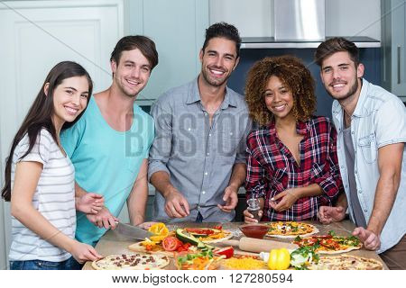 Portrait of happy multi-ethnic friends preparing pizza on kitchen table at home