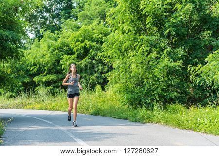 Running girl runner jogging on nature park path during summer training cardio for marathon race or weight loss goal success. Athlete Asian woman with fit body living a happy healthy lifestyle.