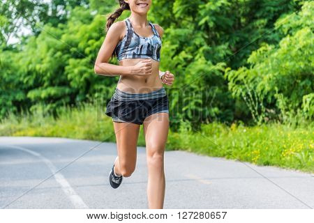 Fitness girl running in summer outdoor park. Happy fit athlete working out in sports bra and 2-in-1 compression shorts fashion activewear outfit showing off slim body and abs training for weight loss.