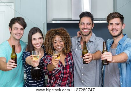 Portrait of multi-ethnic friends showing beer and wine while standing in kitchen at home