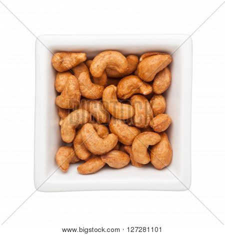 Roasted cashew nuts in a square bowl isolated on white background