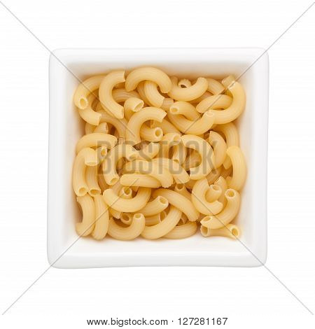 Uncooked elbow macaroni in a square bowl isolated on white background