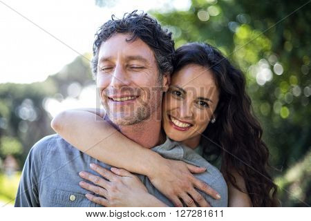 Portrait of smiling happy wife hugging husband at park