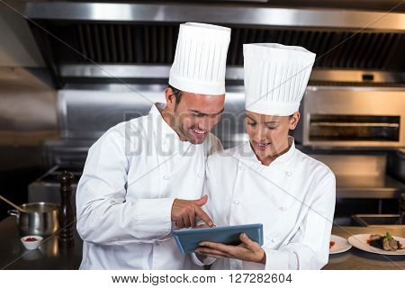 Chefs holding clipboard while standing in commercial kitchen