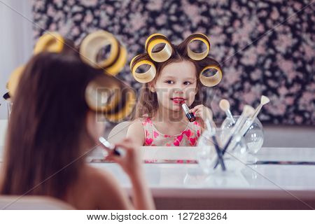 Little girl in hair curlers in a beauty studio