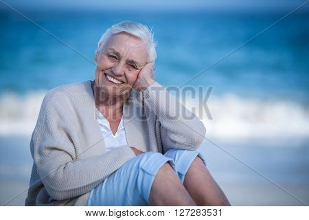 Pretty mature woman day dreaming on the beach