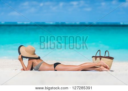 Beach summer vacation woman relaxing sunbathing on white Caribbean sand and turquoise ocean. Young tourist girl lying down on towel by sea wearing bikini and sun hat enjoying summer travel holidays.