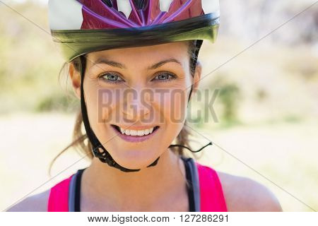 Fit smiling woman wearing helmet in the countryside