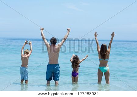 Rear view of family standing with arms raised in shallow water at beach