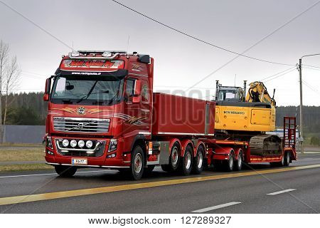 SALO, FINLAND - APRIL 22, 2016: Red Volvo FH16 750 transports New Holland crawler excavator on low bed trailer along highway on rainy evening in South of Finland.