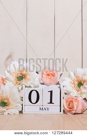 Save Download Preview May 1st. Image of may 1 wooden color calendar on white background with flowers. Spring day, empty space for text. International Workers' Day.