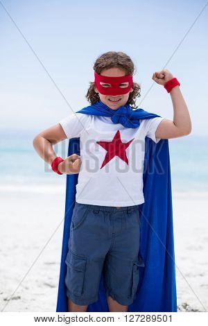 Portrait of boy in superhero costume standing at sea shore against sky