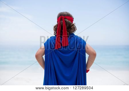 Rear view of boy wearing superhero costume standing at sea shore against sky