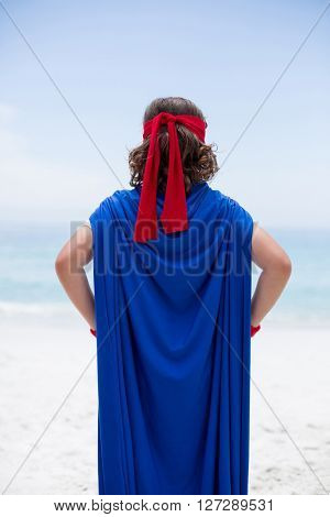 Rear view of boy in superhero costume standing at sea shore against sky
