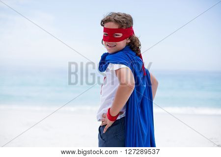 Portrait of boy in superhero costume standing with hand on hip at sea shore