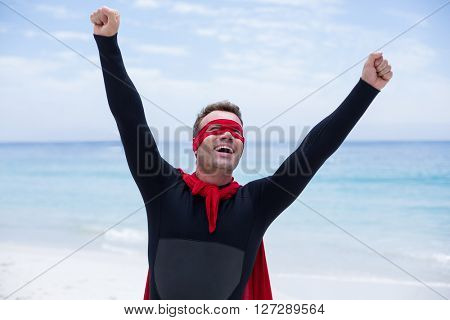 Cheerful man in superhero costume with arms raised at sea shore against sky