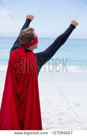 Rear view of man in superhero costume standing with arms raised at sea shore against sky