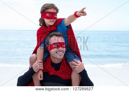 Son in superhero costume pointing while father carrying him on shoulder at beach