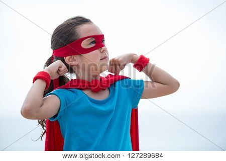 Girl in superhero costume looking away while flexing muscles at beach