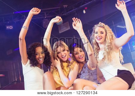 Pretty girls with arms up in a nightclub