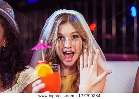 Woman showing her engagement ring in a club
