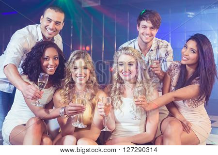 Friends holding champagne glasses in a club