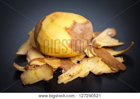 Raw Peeled Potatoes And Potato Peelings On Black Background