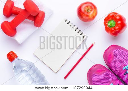 Sport shoes, water, apples and notepad on white background. Healthy life and healthy food concept