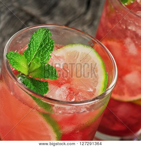 Closeup red cocktail with ice lime and mint on dark wooden background