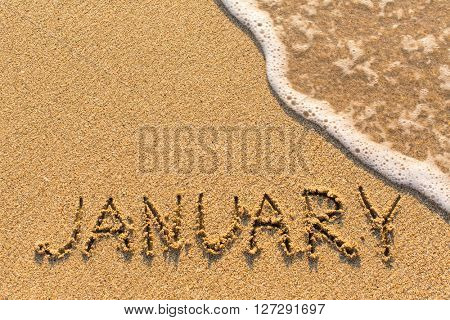 January - word drawn on the sand beach with the soft wave. Months series of 12 pictures.