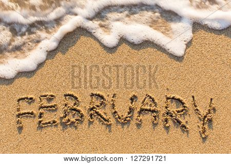 February - word drawn on the sand beach with the soft wave. Months series of 12 pictures.