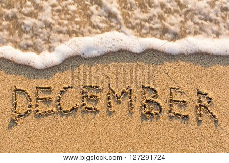 December - word drawn on the sand beach with the soft wave. Months series of 12 pictures.