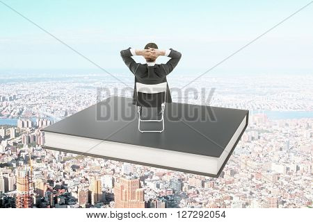 Businessman sitting on a black book soaring over city