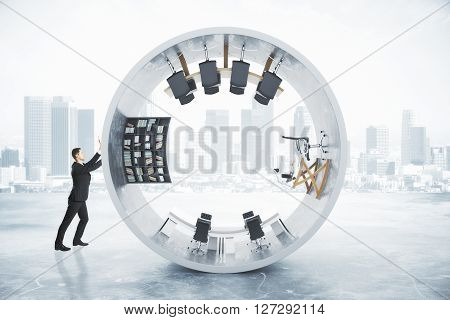 Businessman pushing abstract office interior inside concrete cylinder on foggy city background. 3D Rendering