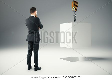 Thoughtful businessman next to white block suspended on crane hook. 3D Rendering