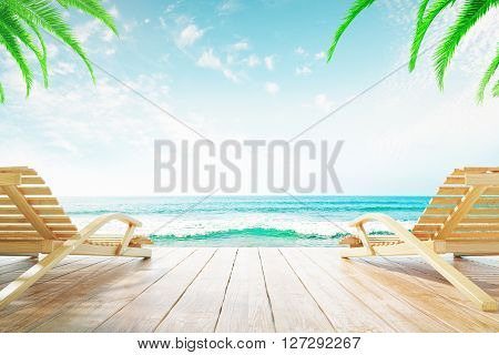 Two chaise longues at the beach with clear skies and palm trees
