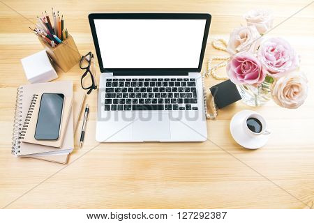 Girly office desktop with blank white laptop screen flowers coffee smartphone and various office tools. 3D Mock up