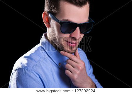 Young Smiling Handsome Man In Sunglasses Thinking About Something Over Black